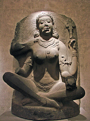 Matrikas - 9th–10th century granite Chola statue of Matrika Maheshvari, seen with a trident in a hand, adorned by serpent ornaments and her vahana (mount), the bull Nandi is seen on her seat — Musée Guimet, Paris.