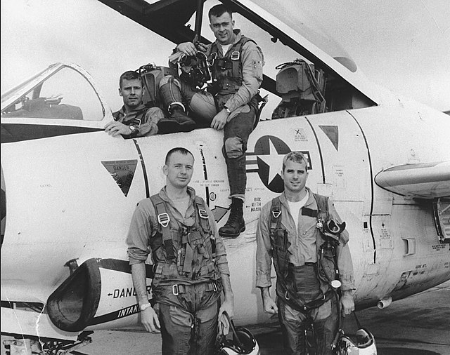 Four military pilots posed in, on, or in front of, silver jet with United States markings