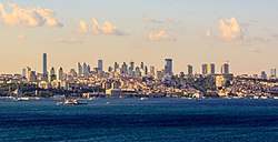 Skyline of a portion of the city, including several skyscrapers interspersed among low- and mid-rises, several historic buildings, parks and hilly terrain, and the waterway known as Bosphorus