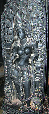 A black stone sculpture of a young topless, standing woman, wearing a conical crown with a halo and various ornaments around her waist, necklaces, bangles, bracelets, earrings, anklets as well as the sacred thread. Her arms are broken. Two small attendants stand with folded hands near her feet.