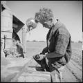 Monterey County, California. Rural youth. Mechanization, the agricultural employee. Checking the oil on a caterpillar... - NARA - 532172.tif