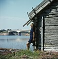 Nainen nojaa hirsirakennukseen, taustalla Marsundin silta.jpg