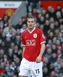 Nemanja Vidić, wearing a red Manchester United jersey with the AIG sponsor logo at the front centre and shorts with a number 15 and Nike logo on the left-leg side, looks forward with his mouth partly opened.