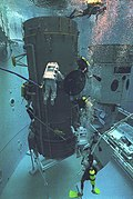 Underwater photograph of the Neutral Buoyancy Space Simulator, showing divers and a full-scale model of a spacecraft in the tank.