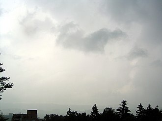 Fractus cloud - A nimbostratus cloud in the background with a stratus fractus in the middle of the upper half of the image.