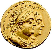 "A gold coin shows paired, profiled busts of a plump man and woman. The man is in front and wears a diadem and drapery. It is inscribed ""ΑΔΕΛΦΩΝ""."