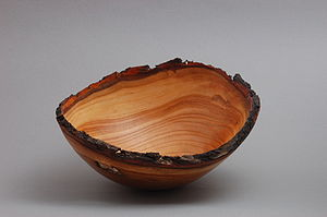 A natural edge turned wood bowl made of peach wood