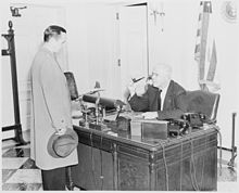 Photograph of White House receptionist William Simmons at his desk, conversing with an unidentified visitor. - NARA - 199477.jpg