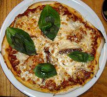 Pizza tonda servita nel piatto e già tagliata in quattro spicchi