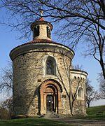 Un bâtiment religieux circulaire, de petite taille, dans un parc.