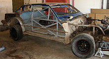 a race car with its body work removed, exposing the metal roll cage