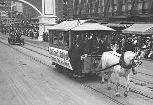 """San Diego Electric Railway - """"Rapid Transit in San Diego"""": An original 1886 horse-drawn trolley and its driver participate in a parade celebrating the groundbreaking of the Panama-California Exposition Center in 1911."""