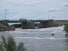 A concrete and metal structure spans a section of choppy water
