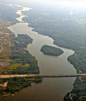 "Rivière des Prairies - Aerial view looking east, of Rivière des Prairies with Louis Bisson Bridge in the foreground. The island ""Ile aux Chats"" can be seen near the center."