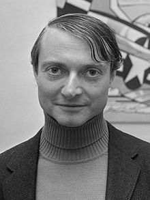 A black-and-white portrait photograph of a man at bust length facing and looking at the viewer while wearing a turtleneck shirt under a blazer all in front of a painting