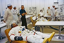 Several men in space suits recline on couches as others stand by.