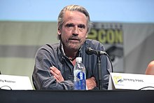 Jeremy Irons seated at a table in front of a microphone with his arms crossed