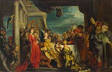 Painting of a banquet with many participants in which a bearded man points to a woman with a cup while a seated woman looks the scene