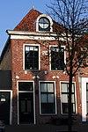 foto van Pand met verdieping, vensternissen en rechte kroonlijst onder zadeldak met dakkapel met ronde fronton