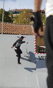 Skateboarder alle prese con una rampa.