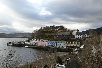 A small harbour fronted with a row of cottages painted in white, pink, green and blue with a tree-covered hillock behind them.