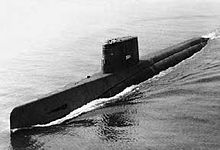 Profile shot of a long, black submarine sailing on the surface.