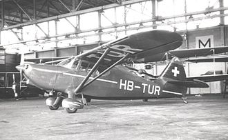Stinson 108 - Swiss Stinson 108-2 at Manchester Airport, England in 1950. This earlier model has the shorter vertical fin with curved trailing edge.