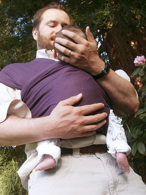 Father holding 7 week old baby in a homemade b...