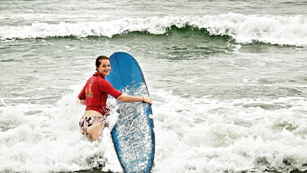 A woman wearing a rash guard while surfing Surfer woman wearing bikini bottom and shirt.png