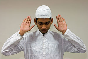 English: A Muslim raises his hands in Takbir, ...