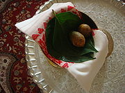 A pair of areca nuts, betel leaves and a 'Gamosa' in a Xorai; this represents cultural symbolism of respect towards the recipient person by the person presenting it