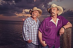 Two grey-haired men wearing cowboy hats, standing in front of the sea at sunset