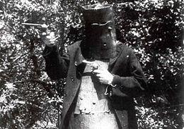 Image en noir et blanc tirée du film; un homme casqué, portant une armure de cuir, tient un pistolet dans chaque main.