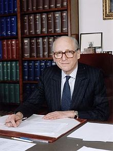 Lord Bingham sitting at his desk with pen in hand and two large bookcases behind him