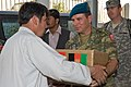 Turkish officer gives a box of food to an Afghan man.jpg