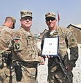 U.S. Army Brig. Gen. Duane Gamble, center, the deputy commanding general of the 1st Sustainment Command, awards a Combat Action Badge to Sgt. Joshua W. Floch, with the 864th Engineer Battalion, assigned to 131007-A-WQ129-006.jpg