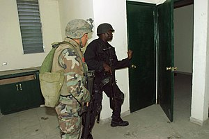 Haitian National Police - A member of the Haitian National Police Special Weapons And Tactics team (right) and a U.S. Marine (left) search an apartment complex in Port-au-Prince in 2004.