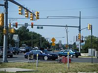 A  congested signalized intersection between two roads. A sign on the traffic light pole reads south left Route 47 north right while a shield in the distance reads south U.S. Route 9.