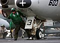 US Navy 050202-N-5345W-012 Aviation Boatswain's Mate 3rd Class Robert Lightner signals to have the catapult shuttle moved forward in order to place an E-2C Hawkeye into tension.jpg