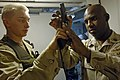 US Navy 061118-N-8148A-271 U.S. Navy Gunner's Mate Seaman Randy Barnes, left, assigned to Mobile Security Squadron Three (MSS-3), shows Chief Master at Arms Cephia Batson that his 9mm pistol is clear and safe to holster during.jpg
