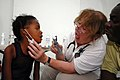 US Navy 070902-N-8704K-139 Carole Ferguson, a Project Hope volunteer attached to Military Sealift Command hospital ship USNS Comfort (T-AH 20), provides medical care for Sofia Etinne at Hopital De L'universite D'etat D'Haiti.jpg