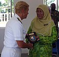 US Navy 080716-N-4431B-737 Rear Adm. Nora W. Tyson, commander, Logistics Group Western Pacific, presents a plaque to the headmistress of the Sekolah Kebangsaan Kijal elementary school.jpg