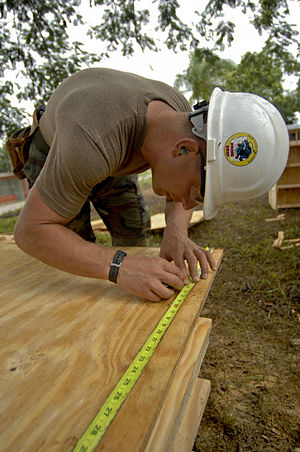 US Navy 081013-N-9620B-010 Hospital Corpsman Chief Casey Jacobs%2C embarked aboard the amphibious assault ship USS Kearsarge %28LHD 3%29%2C measures a sheet of plywood to make bookshelves for the school Presbitero Carlos Novel