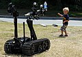 US Navy 090712-N-1688B-130 A child plays tag with a remote-controlled robot from Explosive Ordnance Disposal Mobile Unit (EODMU) 2, Detachment Yorktown, during the Yorktown Waterman's Heritage Festival in Yorktown, Va.jpg