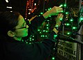 US Navy 091208-N-2523E-158 Interior Communications Electrician 2nd Class Jessica Valle tapes Christmas lights onto metal lettering aboard the Nimitz-class nuclear aircraft carrier USS Harry S. Truman (CVN 75).jpg