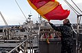 US Navy 110425-N-QP268-032 Quartermaster Seaman Christopher Koch hoists the Romeo flag aboard the amphibious dock landing ship USS Whidbey Island (.jpg