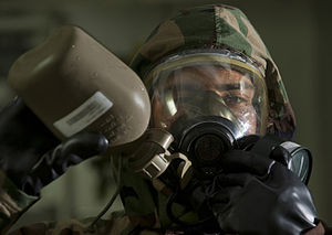 US Navy 111212-N-DR144-296 Yeoman 3rd Class Andrew Velasquez drinks from a canteen while wearing an MCU-2P protective mask.jpg