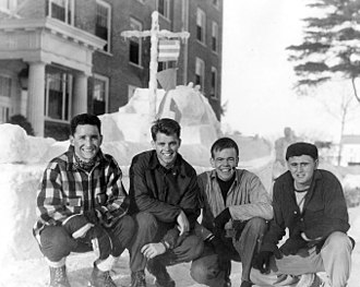 V-12 Navy College Training Program - Robert F. Kennedy (second from left) completing his V-12 studies at Bates College in Lewiston. Pictured in background: a snow replica of a Naval boat.