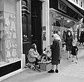 Vrouw geeft geld aan een straatmuzikante en haar twee honden, Bestanddeelnr 254-0346.jpg