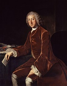 An oil painting of William Pitt the Elder wearing a red velvet suit and powdered wig, seated at a desk and holding a letter.